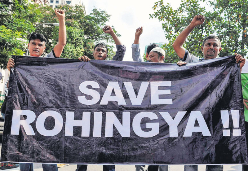 Ethnic Rohingya refugees from Myanmar residing in Malaysia hold a banner during a protest outside the Myanmar embassy in Kuala Lumpur on May 21, 2015.