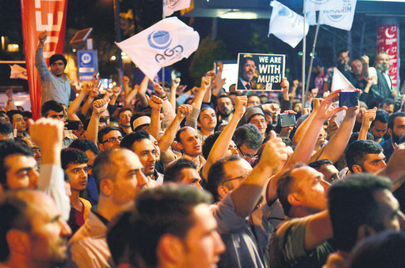 Protestors hold pictures of ousted Egyptian President Morsi and they shout slogans during a pro-Morsi rally in front of the Egyptian consulate in Istanbul.