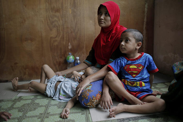 Ethnic Muslim Rohingya child, Mobinakhatu (R) and his family in their community meeting house in Kuala Lumpur, 19 May 2015 (EPA Photo)