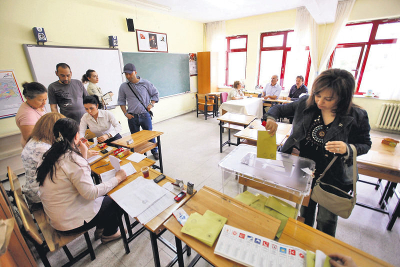 A woman casts her vote as others wait in line at a polling station in Ankara for the 2011 general elections.