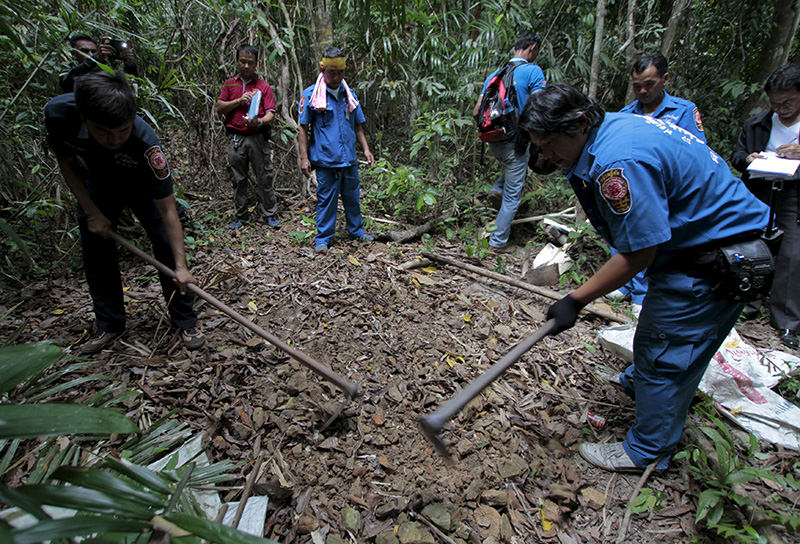 Security forces and rescue workers inspect a mass grave at a rubber plantation near a mountain in Thailand's southern Songkhla province May 7, 2015 (Reuters Photo)