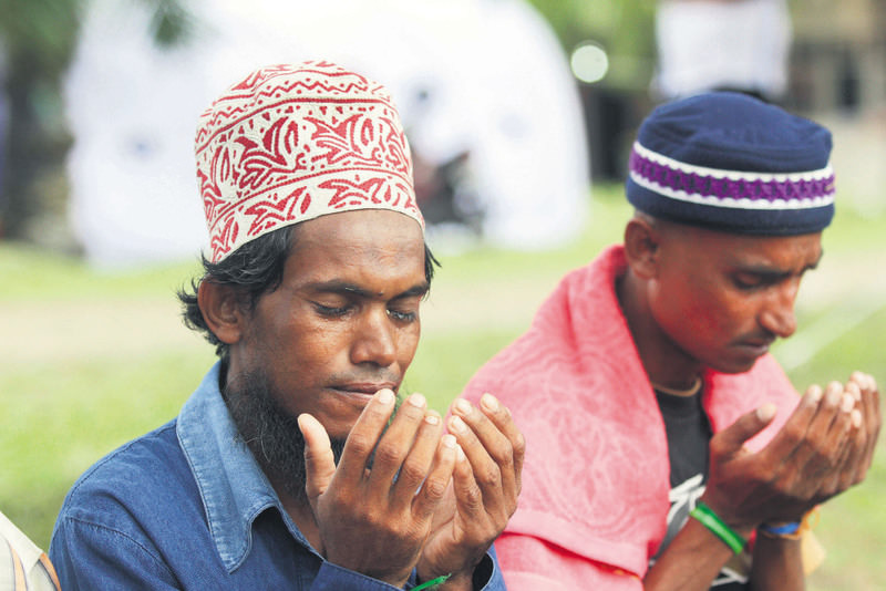 Two Rohingya Muslims pray at a religious ceremony held in Myanmar to pray for the Rohingyas stranded at sea.