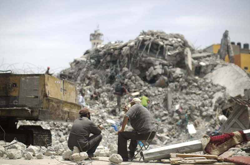 Palestinian men sit amid the rubble of houses which were destroyed during the 50-day war between Israel and Hamas militants in the summer of 2014, in the Eastern Gaza City Shujaiya neighbourhood, on May 23, 2015 (AFP Photo)