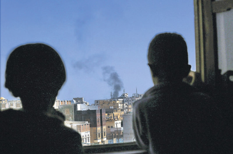 Yemeni boys watch black smoke rising above a neighborhood following airstrikes carried out by the Saudi-led alliance targeting a Houthi-controlled military base in Sana'a.