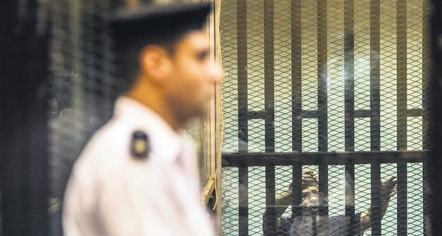 Ousted Egyptian President Mohammed Morsi (R), who was recently sentenced to death, gestures during his new trial in Cairo. (AFP Photo)