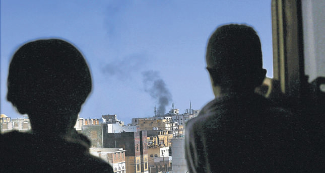Yemeni boys watch black smoke rising above a neighborhood following airstrikes carried out by the Saudi-led alliance targeting a Houthi-controlled military base in Sana'a. (AFP Photo)
