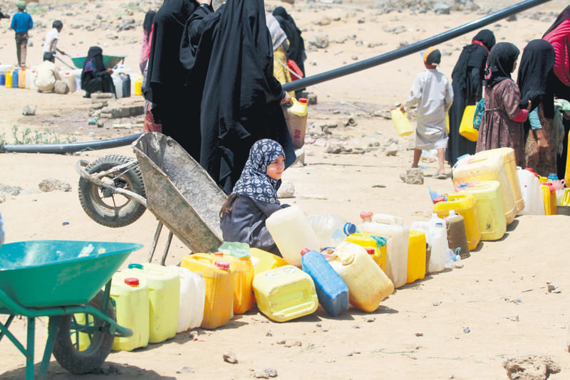 People wait to collect water from a public tap amidst an acute water shortage in Sanaa.