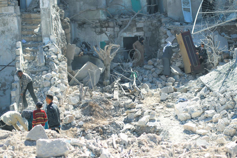 Residents search for belongings amidst rubble at a site hit by what activists said were barrel bombs dropped by forces loyal to Syria's President Bashar Assad in Ain Larouz village in the Jabal al-Zawiya region of Idlib province.