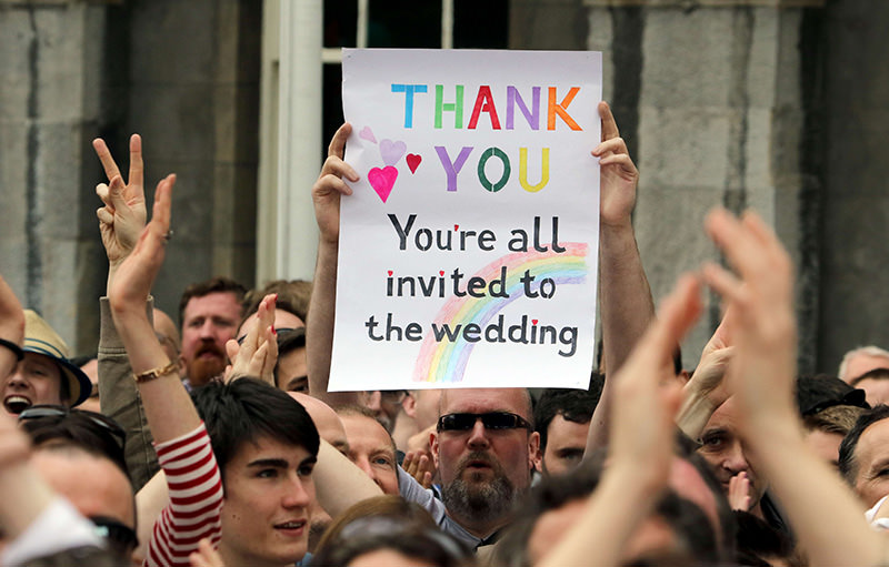 A supporter holds a sign reading 'Thank You - You're All Invited to the Wedding' as he celebrates outside Dublin Castle following the result of the same-sex marriage referendum in Dublin on May 23, 2015 (AFP Photo)