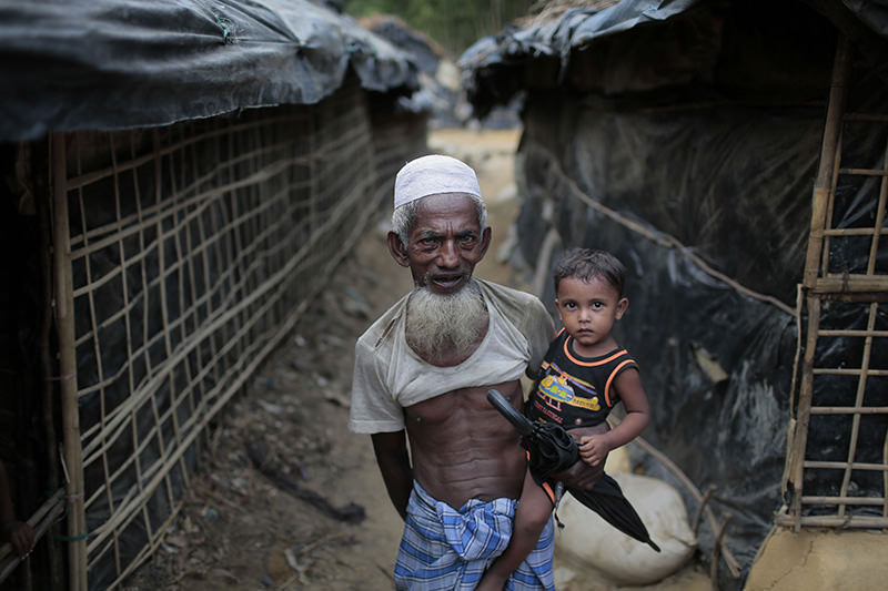 An elderly Rohingya Muslim man carries his grandson as they walk in an alley at a camp for Rohingya people in Ukhiya, near Cox's Bazar, 296 kilometers (183 miles) south of Dhaka, Bangladesh (AP Photo)