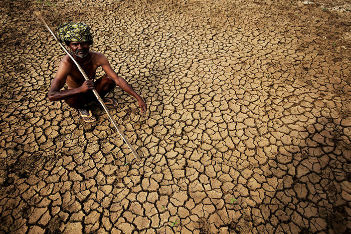An Indian farmer sits in his dried up land in gauribidanur village, doddaballapur district, which is very close to Karnataka and Andhra Pradesh border around 85km from Bangalore, Indian, 26 May 2015 (EPA Photo)
