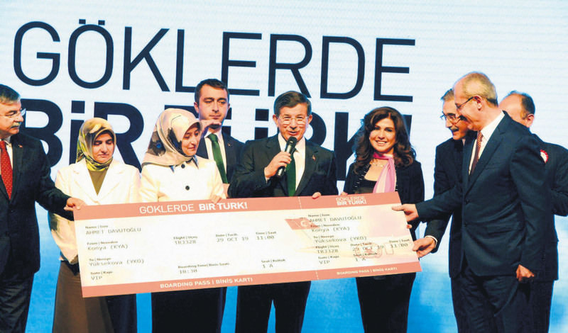 Prime Minister Davutou011flu receives a symbolic ticket from Fatih u00d6zmen, chairman of Sierra Nevada Corporation, during the intoductory meeting of the first domestic airplane project.