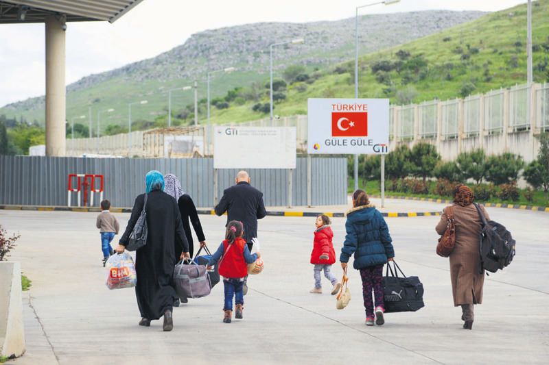 Syrians walking toward the Cilvegu00f6zu00fc border crossing to enter Syria against the backdrop of a sign reading ,goodbye, in Turkish.
