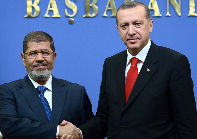 Turkey's then Prime Minister Tayyip Erdogan (R) and his guest, Egypt's President Mohamed Mursi greet the audience during the AKP congress in Ankara on September 30, 2012 (AA Photo)