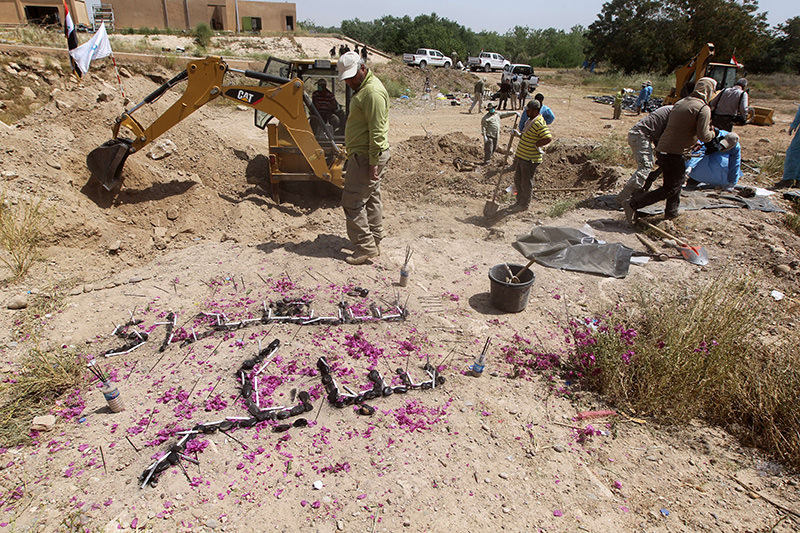 A small memorial reading in Arabic, , the martyrs of Speicher, is seen as members of the Iraqi security forces inspect a mass grave containing the remains of people in the city of Tikrit, on April 12, 2015 (AFP Photo)