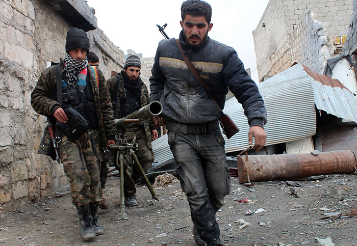 Opposition fighters carrying a rocket launcher during clashes against government forces in the Sheikh Lutfi area, west of the airport in the northern Syrian city of Aleppo (