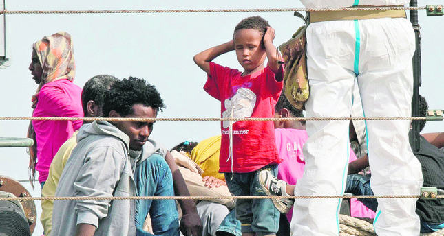 Migrants disembark from an Italian military ship as they arrive in the port of Augusta on the eastern coast of Sicily last week. (AFP Photo)