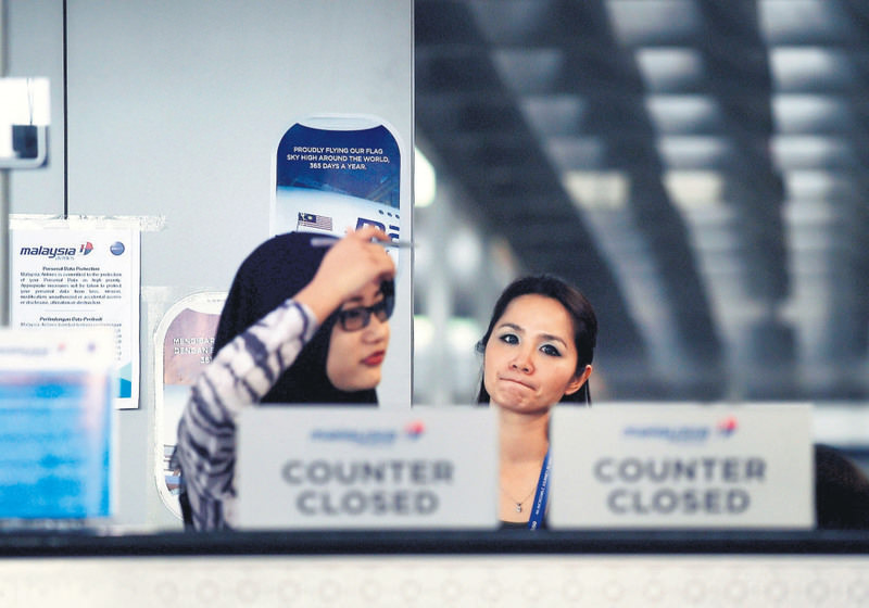 Malaysia Airlines employees stand behind a closed-counter at the departure terminal of the Kuala Lumpur International Airport in Sepang yesterday.