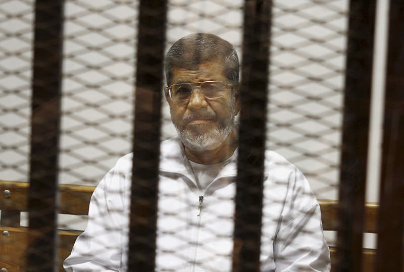 Mohammed Morsi sits in a defendant cage in the Police Academy courthouse in Cairo, Egypt (AP Photo)