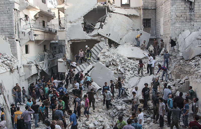 People gather at the scene after Syrian government forces allegedly dropped barrel bombs on the northern Syrian city of Aleppo, on May 30, 2015 (AFP Photo)