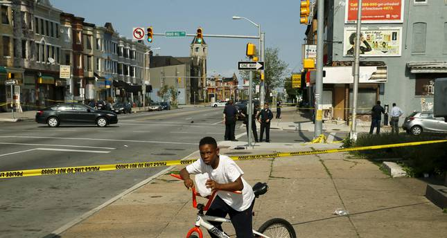 A young boy is stopped by police tape at the scene of a shooting where two men were shot at the intersection of West North Avenue and Druid Hill Avenue in West Baltimore, Maryland May 30, 2015 (Reuters Photo)