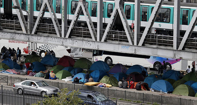An elevated metro passes over a bridge which provides shelter for migrants who have established a make-shift tent city in Paris France, May 29, 2015 (Reuters Photo)