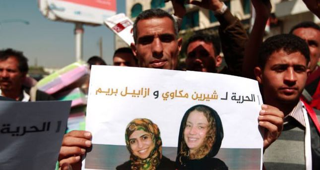 A Yemeni man holds a sign which says Freedom to Isabelle Prime and Shereen Makawi (AFP Photo)