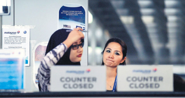 Malaysia Airlines employees stand behind a closed-counter at the departure terminal of the Kuala Lumpur International Airport in Sepang on Monday. (AFP Photo)