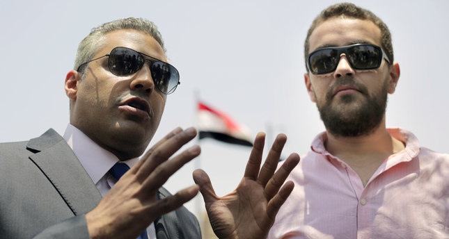 Al-Jazeera English journalists Mohammed Fahmy, left, and Baher Mohammed, speak to reporters after a hearing in their retrial outside a courtroom of Tora prison, in Cairo, Egypt, Monday, June 1, 2015. (AP Photo)