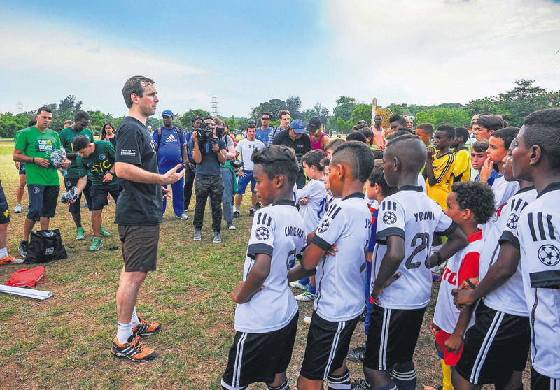 A New York Cosmos player speaks to children from Cuban football teams in Havana.