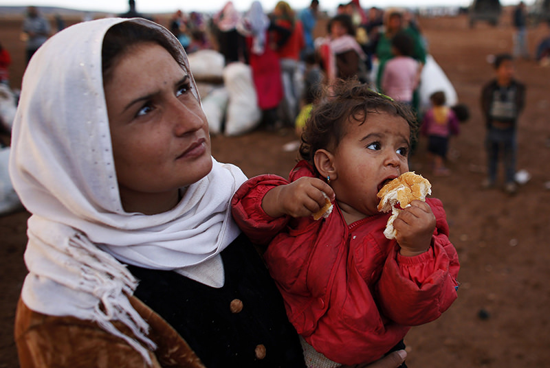 A Syrian Kurdish refugee woman with her daughter waits for transportation after crossing into Turkey from the Syrian border town Kobani, near the southeastern Turkish town of Suruu00e7 (Reuters Photo)