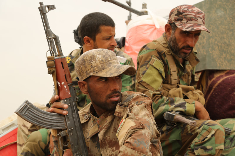 Fighters from the Badr Brigades Shiite militia patrol at the front line on the outskirts of Fallujah, Anbar province, Iraq, Monday, June 1, 2015 (AP Photo)
