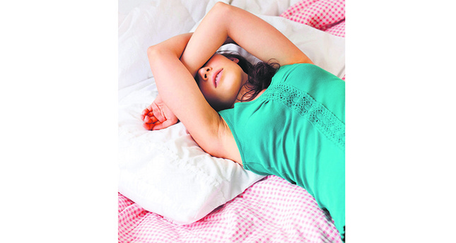 Exhausted teenage, girl sleeping on bed (Image by © Tetra Images/Corbis)