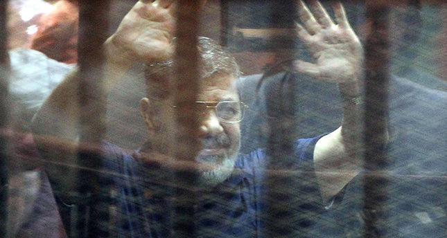 A file photo dated 16 May 2015 showing Mohamed Morsi, gesturing from inside a cage in the courtroom where he stood trial in Cairo, Egypt (EPA Photo)