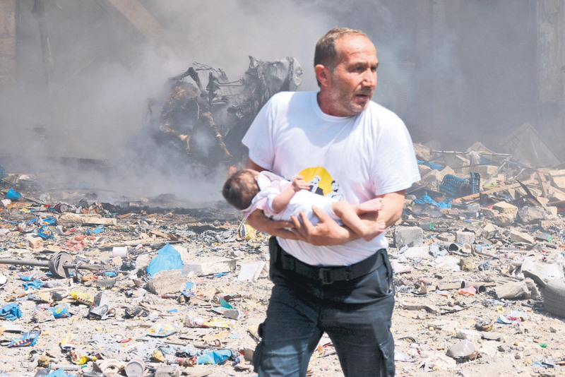 A man holds a baby that survived what activists said was a site hit by a barrel bomb dropped by the Assad regime in the old city of Aleppo on Wednesday.