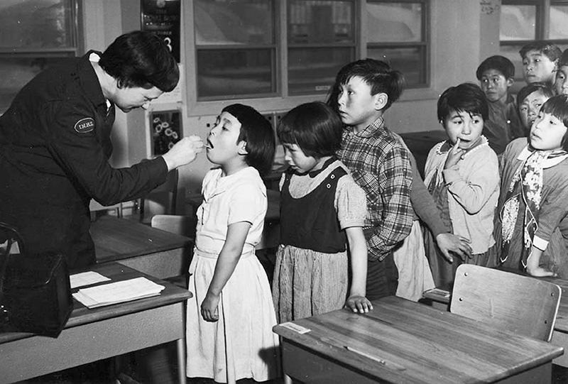 Nurse Desrochers checks a girl's throat while other children wait in line, at the Frobish Bay Federal Hostel in Nunavut, Canada in a 1959 archive photo (Reuters)