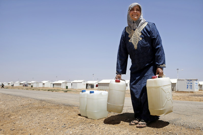 Syrian refugee Siham Hamish, 43, carries water containers at Azraq refugee camp, Jordan. (AP Photo)