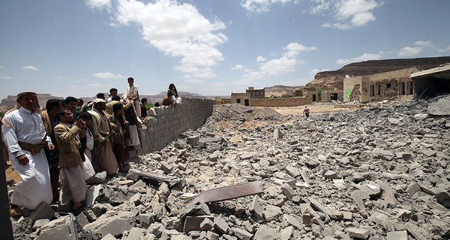 People look on, near the site of a building destroyed by a Saudi-led air strike near Sanaa, May 30, 2015 (Reuters Photo)