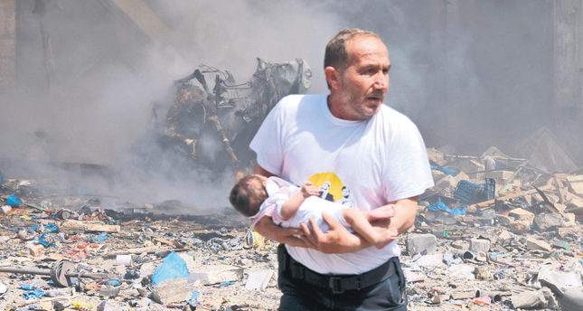 A man holds a baby that survived what activists said was a site hit by a barrel bomb dropped by the Assad regime in the old city of Aleppo on Wednesday. (Reuters Photo)