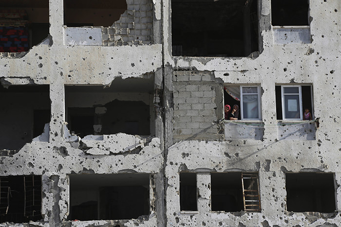 Palestinians look through their apartment damaged by Israel's attack on Gaza last summer's, in the residential neighborhood of Beit Lahiya in the northern Gaza Strip, Tuesday, June 2, 2015. (AP Photo)