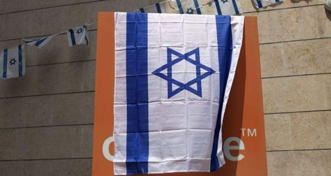 Orange signs were covered by the Israeli flag in several cities in protest at the Orange CEO's remarks (AP Photo)