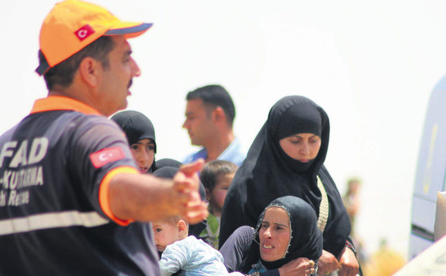 An AFAD official gesturing to Syrian women as they cross into Turkey. More Syrians fleeing the clashes between Kurds and ISIS are expected to enter Turkey. (AA Photo)