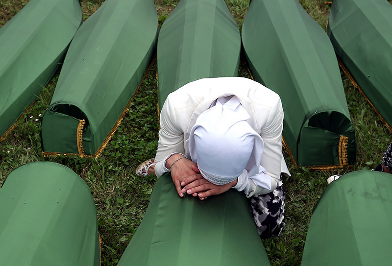 A Bosnian Muslim woman weeping over a casket at the Potocari Memorial Center during the funeral in Srebrenica, Bosnia and Herzegovina, where 175 newly-identified Bosnian Muslims were buried (EPA Photo)