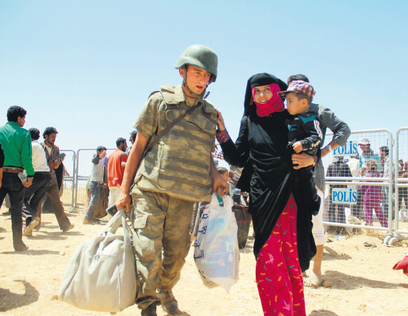 A Turkish soldier carrying a Syrian woman's bags as she crosses into Turkey from Syria. Hundreds entered Turkey over the past few days while more people head to the border with the conflict escalating in Syria.