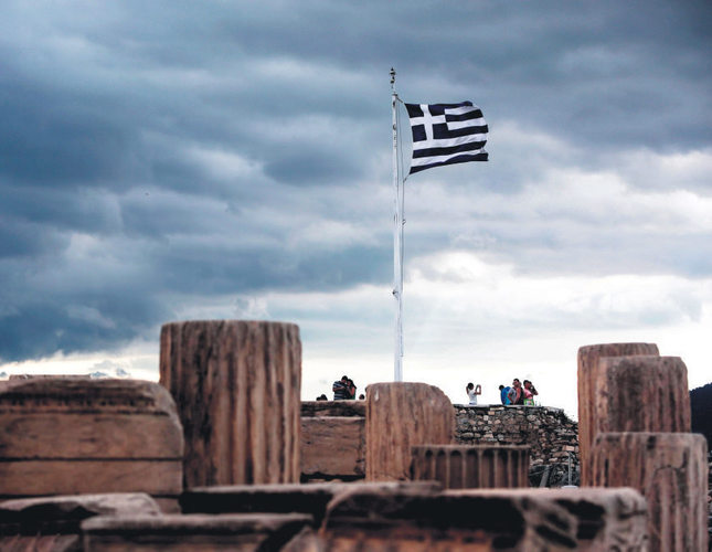 A Greek flag waves in the breeze at the Acropolis in Athens on Friday. Greece bought time in debt crisis negotiations with official creditors when it moved to bundle four looming IMF loan payments into one to be paid by the end of June.