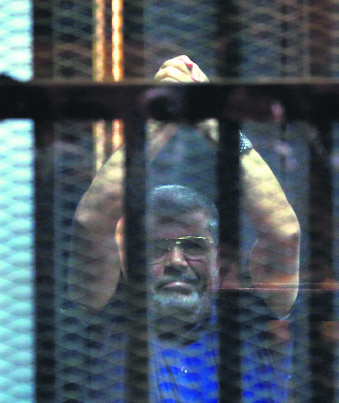 Ousted Egyptian President Morsi poses behind bars.