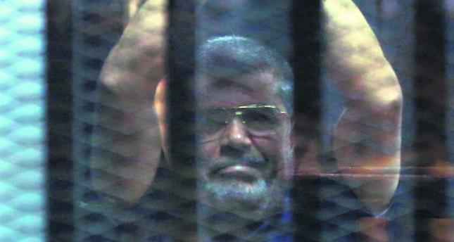 Ousted Egyptian President Morsi poses behind bars.