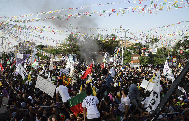 People look at smoke from an explosion which injured several people during a rally by the pro-Kurdish People's Democratic Party (HDP) on June 5, 2015 in Diyarbakir (AFP Photo)