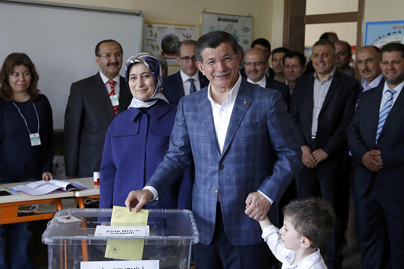Turkey's PM Davutou011flu casts his vote next to his wife Sare (L) as he holds his nephew Eren Alp u00c7alu0131k at a polling station in Konya (Reuters Photo)