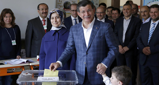 Turkey's PM Davutoğlu casts his vote next to his wife Sare (L) as he holds his nephew Eren Alp Çalık at a polling station in Konya (Reuters Photo)